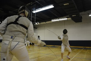 Youth fencers spar with each other during a class at Birmingham Fencing Club.